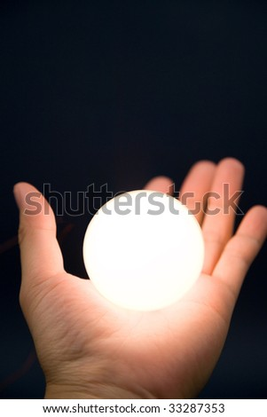 Hand holding a bright ball, Concept of magic - stock photo