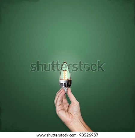 Hand holding a bright LED light bulb in front of a green chalkboard with plenty of copy space - stock photo
