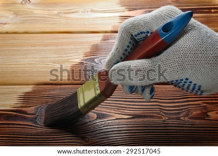 Hand holding a brush applying paint on a wooden surface - stock photo
