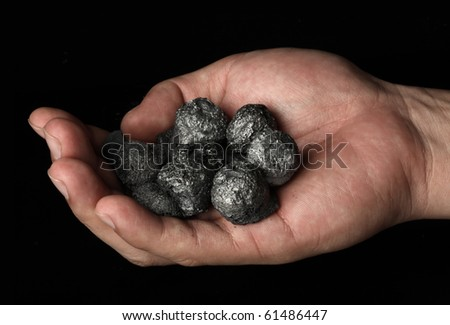 Hand holding a bunch of coal - stock photo