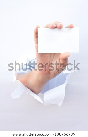 Hand holding a business card breaking through the hole in white background