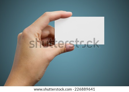 Hand holding a business card on a blue background