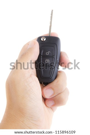 Hand holding a car key on white background.