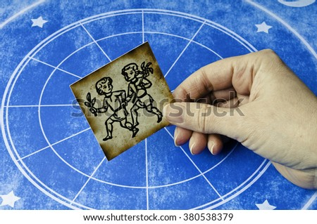hand holding a card with sign of gemini - stock photo