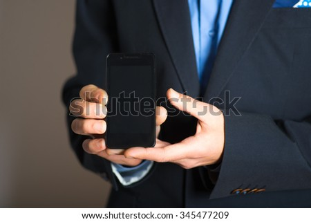 Hand holding a cell phone. advertising or business concept, isolated on a gray background.