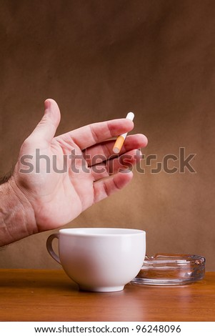 Hand holding a cigarette and a cup ashtray. - stock photo