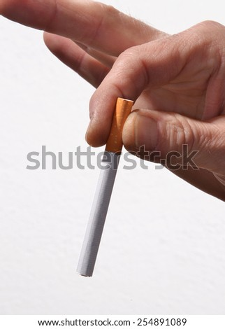 Hand holding a  cigarette butt isolated on White background. - stock photo