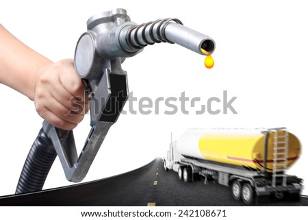 Hand holding a classic fuel nozzle pumping and truck with fuel tank in motion blur on the highway - stock photo