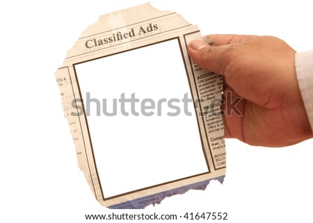 Hand holding a classified ads- many uses in the employment and resources. - stock photo