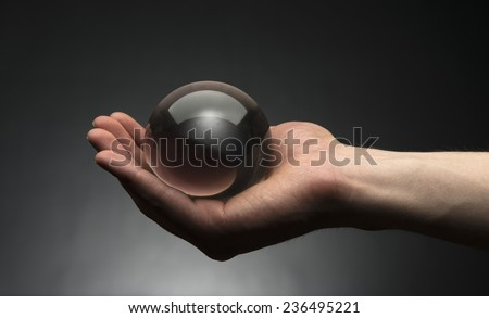 Hand holding a clear transparent crystal glass ball in their palm - stock photo