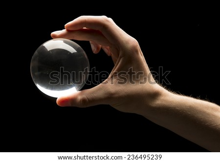 Hand holding a clear transparent crystal glass ball isolated on black background