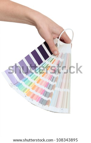 Hand holding a colour chart - stock photo
