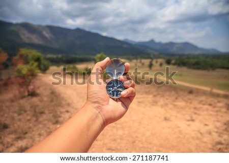 Hand holding a compass - stock photo