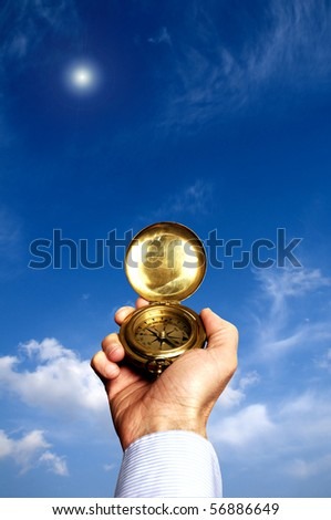 hand holding a compass in front of a blue sky