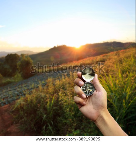 Hand holding a compass on sunset background. - stock photo