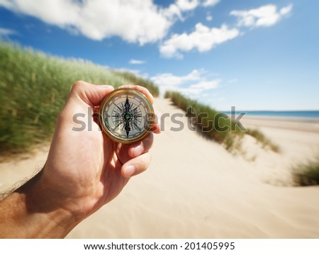 Hand holding a compass on the beach by sea concept for guidance, direction, and adventure - stock photo