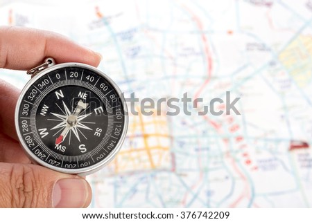 hand holding a compass on the map background - stock photo