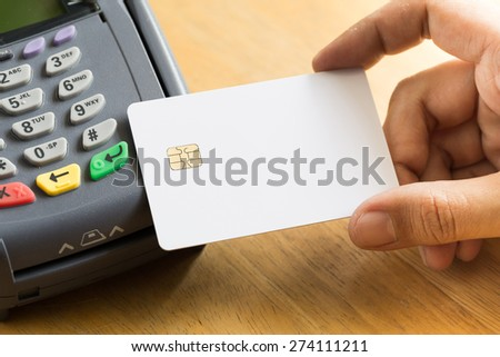 hand holding a credit card with credit card machine - stock photo