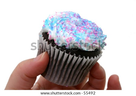 Hand holding a cupcake with whipped icing and pink and blue sugar sprinkles. - stock photo