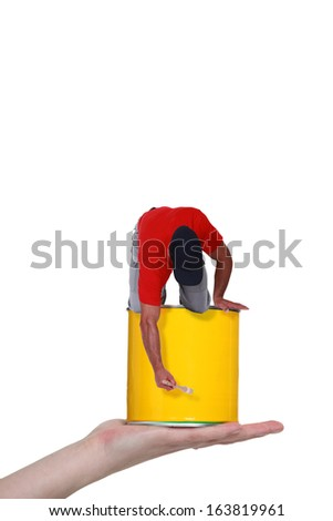 Hand holding a decorator on a pot of paint - stock photo