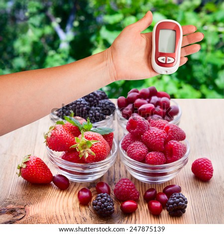 Hand holding a device for measuring blood sugar. The concept of proper nutrition and diet in diabetes. Berries in plates. - stock photo