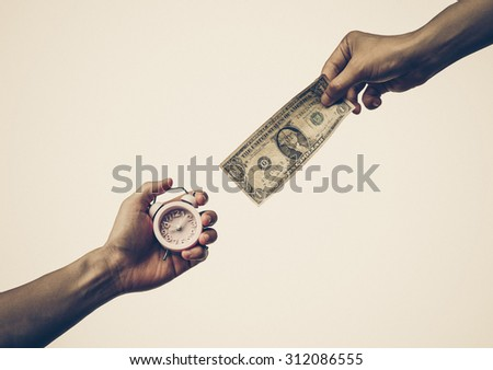 hand holding a dollar banknote trying to buy a clock / Buying time - stock photo