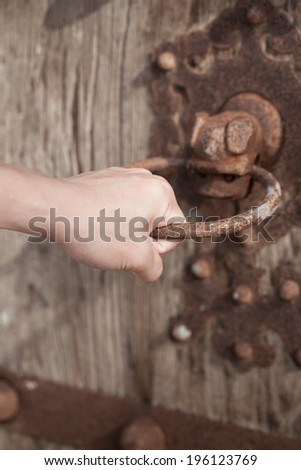 hand holding a door knocker