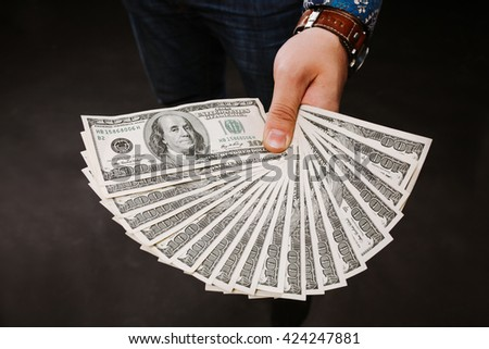Hand holding a fan of dollars. One hundred dollars banknotes bundle, lot dollars, lot of banknotes. - stock photo
