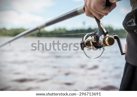 hand holding a fishing rod with reel. Focus on Fishing Reels  - stock photo