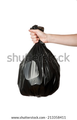 Hand holding a full black plastic trash bag - stock photo