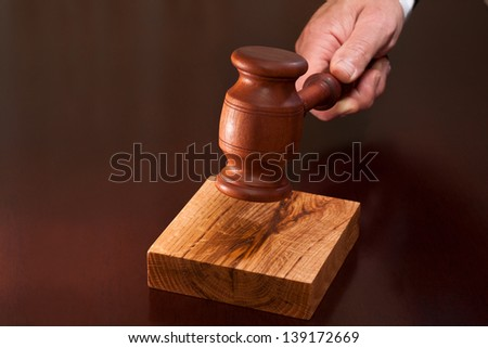 Hand holding a gavel against the table - stock photo