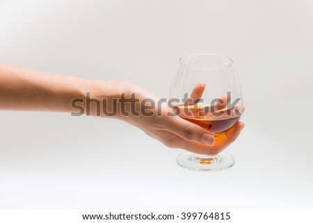 Hand holding a glass of brandy - stock photo