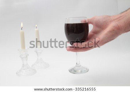 Hand holding a glass of Kiddush on Shabbat, Shabbat candles, and a table with a white tablecloth in accordance Shabba - stock photo
