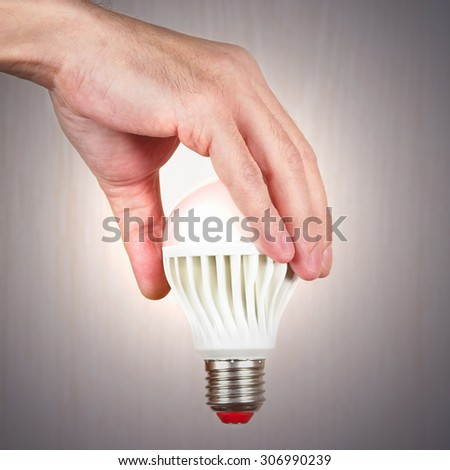 Hand holding a glowing ecofriendly bulb on a light wood background - stock photo
