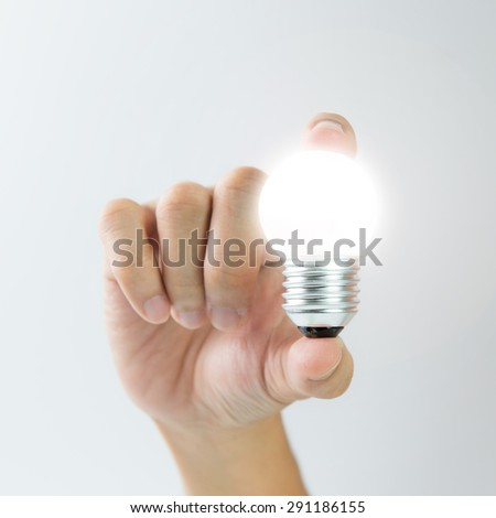 Hand holding a glowing light bulb over white background for innovation conceptual - stock photo