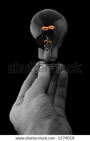 Hand Holding a Glowing Lightbulb on Black Background - stock photo