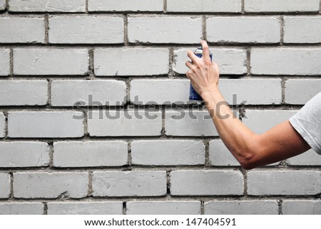 hand holding a graffiti spray can in front of a brick wall - stock photo