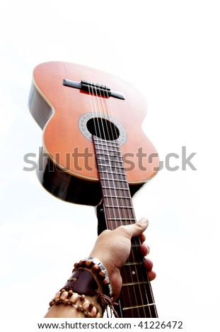 Hand holding a guitar over white background - stock photo