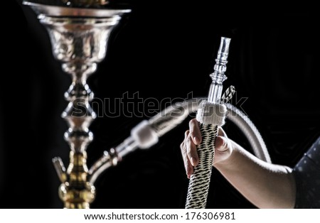 hand holding a hookah pipe - stock photo