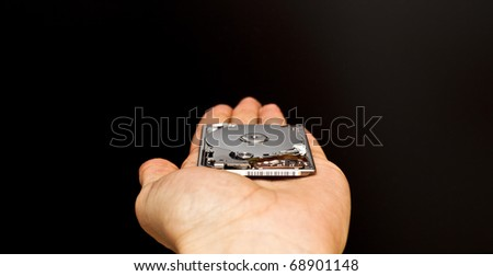 Hand holding a 1.8 inch hard disk drive on black background