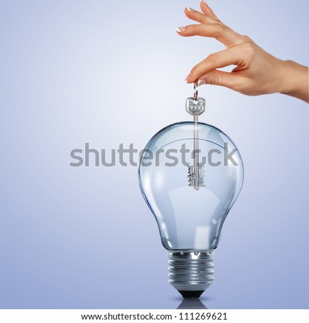 Hand holding a key and putting it inside a light bulb - stock photo