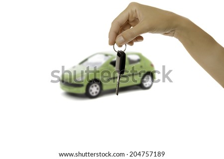 hand holding a key car and a car on the background isolated on a white background - stock photo