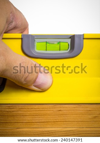 Hand holding a level against wood surface indicating it is level. - stock photo