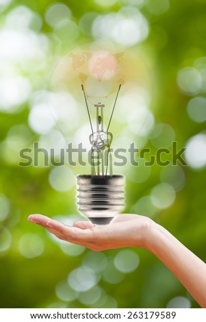 hand holding a light bulb on green bokeh background - stock photo