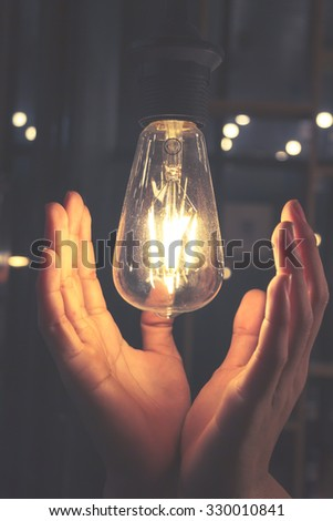 Hand holding a light bulb represents a rather dark and abstract concepts, and the picture colored vintage.