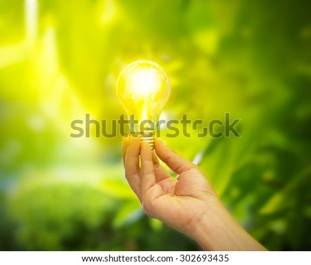 hand holding a light bulb with energy on fresh green nature background, soft focus - stock photo