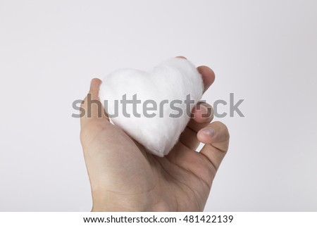Hand holding a light cotton wool heart shape. Caring concept