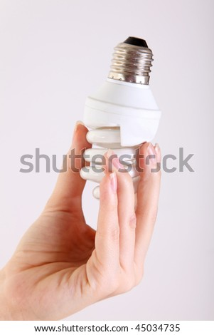 Hand holding a lightbulb on a white background - stock photo