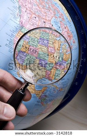 Hand holding a magnifying glass above an earth globe. - stock photo