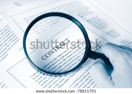 hand holding a magnifying glass examing a business contract - stock photo